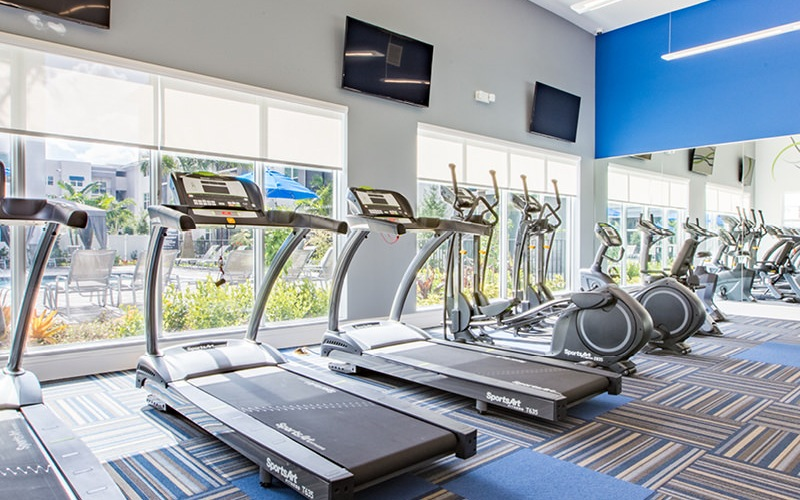 bright fitness center with large windows and fluorescent lighting
